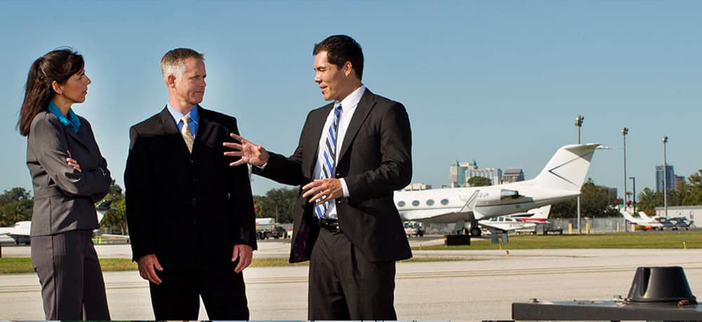 Two men and a woman talk in front of a commercial airliner.